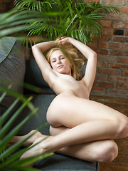Erotic picture of Runa bares her nubile body as she poses on the couch.