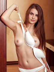 Erotic picture of Bella Libre poses by the door baring her erect nipples and sweet pussy.