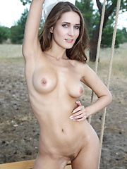 Erotic picture of Elina poses on the swing as she bares her sexy body and trimmed pussy.
