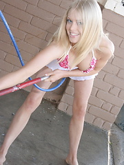 Erotic picture of Skye and her cute petite friend show off in skimpy bikinis at the car wash