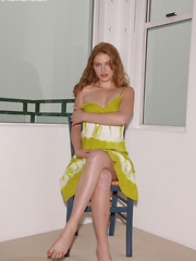 Erotic picture of Stormy Rose strips off her sexy, green dress on the chair showing her gorgeous, perky tits